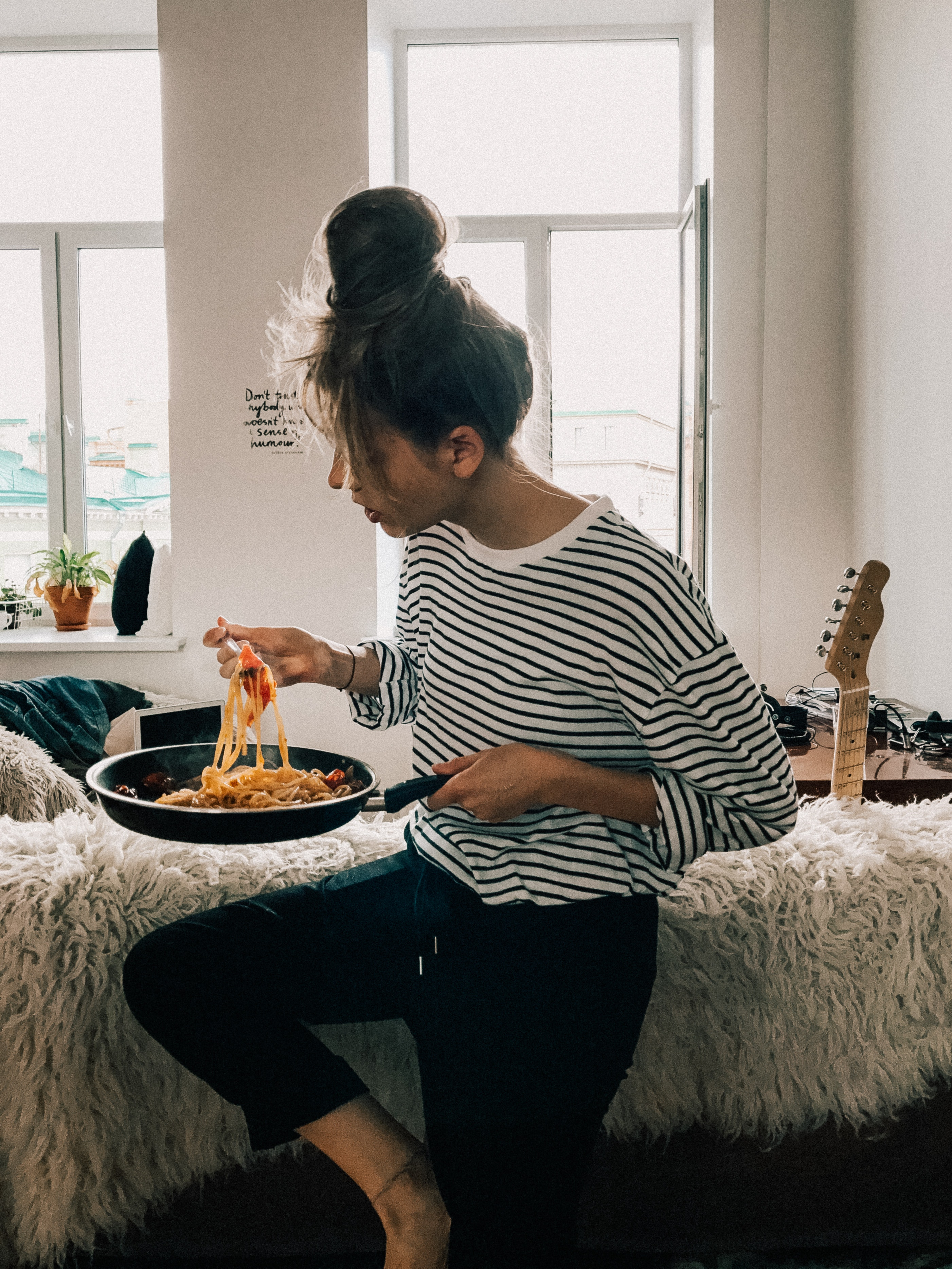 women in striped shirt eating pasta in apartment