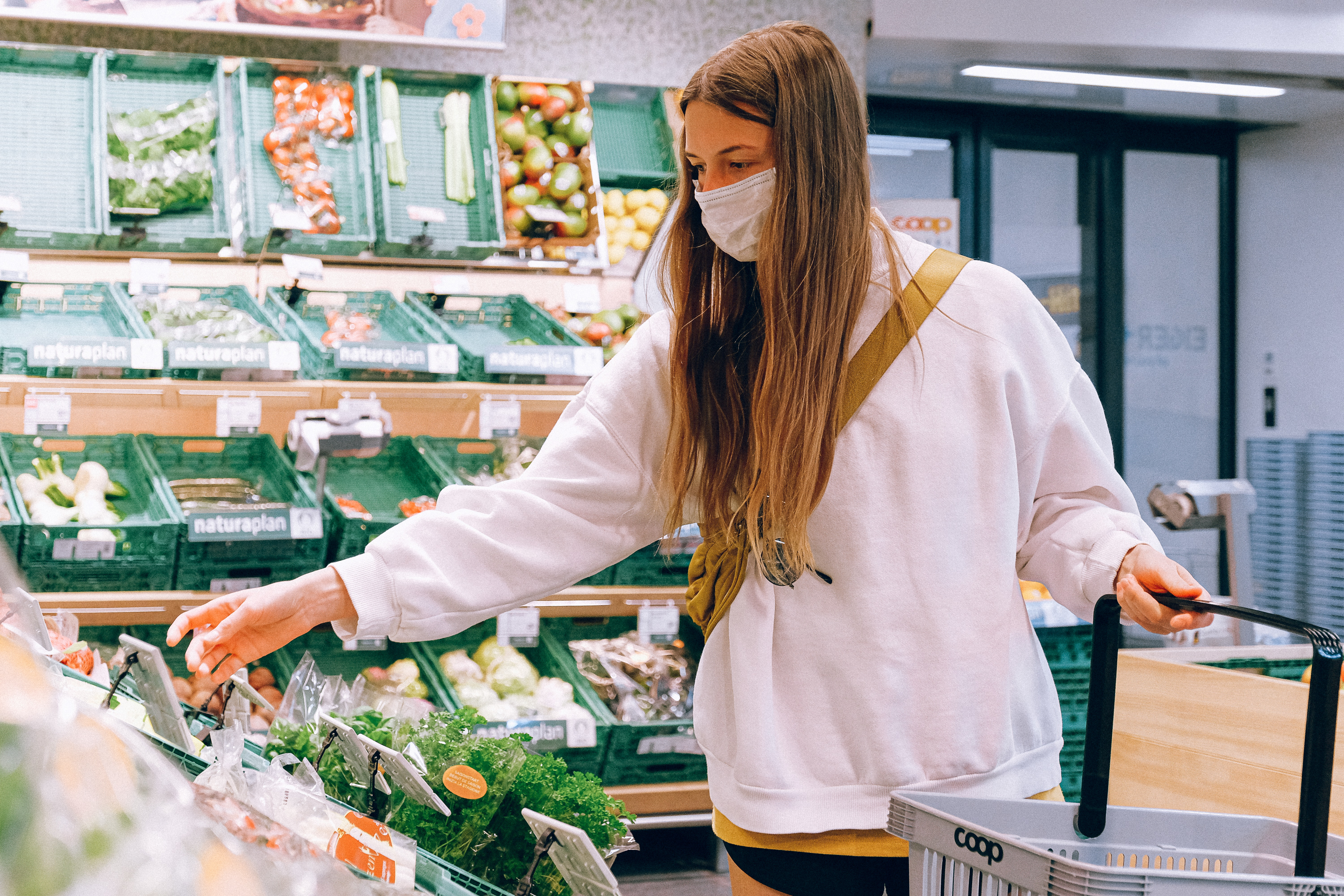 Women in white shirt and mask shopping at grocery store